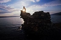 Man sitting on rock overlooking ocean
