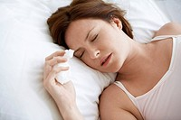 Woman lying in bed with cold close up