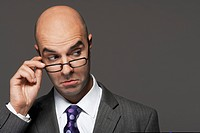 Balding businessman hand on glasses making a face