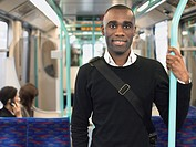 Smiling Commuter Standing on Train holding bar