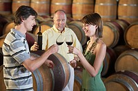 Three people wine_tasting beside wine casks