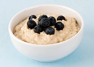 A bowl of porridge with fresh blueberries