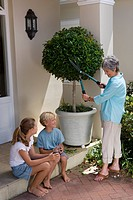 Mother pruning tree in pot, smiling at son and daughter 8_12