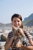 Woman holding dog on beach, smiling, portrait, close_up