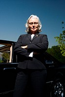 Businesswoman posing near car