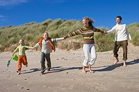 Family running on beach (thumbnail)