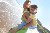 Portrait of mother piggybacking daughter on beach (thumbnail)