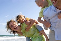 Parents piggybacking children on beach