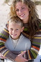 Portrait of mother embracing son on beach