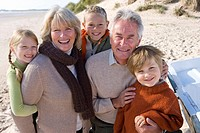 Portrait of grandparents with grandchildren on beach