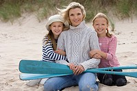 Portrait of mother and daughters on beach with oars