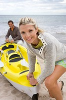 Young couple with kayak on beach