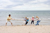 Young family playing tug of war at beach