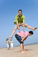 Young man leaping over friend at beach (thumbnail)