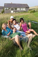 Portrait of young adults sitting in front of house