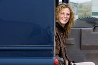 Portrait of happy young woman sitting in van