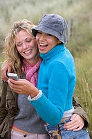 Portrait of young women with phone outdoors