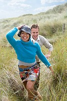 Young happy couple running through grass at beach