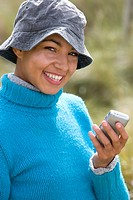 Young mixed race woman holding phone