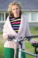Portrait of young woman with bicycle outdoors