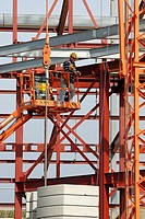 Worker operating hydraulic lift on construction site, Aberystwyth, Wales