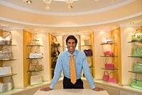 Salesman posing in front of purses