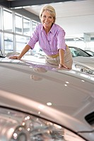 Woman looking at new cars in showroom