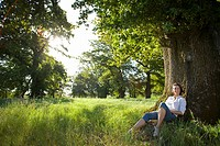 Woman sitting by tree