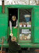 Woman selling vegetables from small grocery van in a market in Yuzhno Sakhalinsk on Sakhalin Island in Russia
