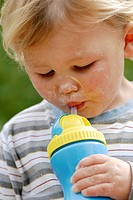 Young boy with a messy face drinking from a plastic beaker