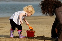 Toddler on the beach making a sandcastle under adult supervision, Wales