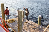 Young fishermen in plaid shirts standing on pier with rope near fishing boat