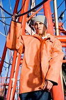 Young fisherman in orange raincoat on fishing boat