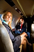 Businessman and businesswoman sitting on small private jet