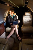 Businesswoman sitting in small private jet plane