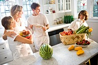 Young family in kitchen with fresh fruits and vegetables