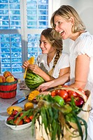 Mother and daughter in kitchen with fresh fruits and vegetables