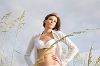 Young woman in white bikini top standing on beach with sea oats