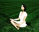 Woman meditating on meadow