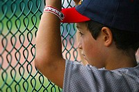Boy looking at a baseball field through a fence in little league