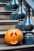 Halloween Jack-O-Lantern, carved pumpkin, on the steps of a brownstone home