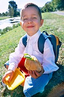 Boy with sandwich on the grass