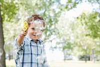 Little boy playing with soap bubble gun