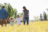 Couple strolling through meadow with small daughters