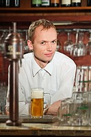 Barman pouring beer at pub