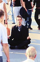 Man meditating on the street
