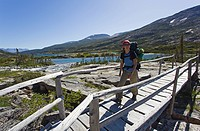 Young woman hiking, backpacking, crossing a wooden bridge, hiker with backpack, historic Chilkoot Pass, Chilkoot Trail, Deep Lake behind, Yukon Territ...