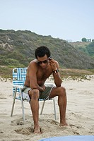 Mixed race man talking on cell phone on beach