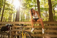 Hispanic cyclist sitting on bridge railing