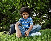 Mixed race boy sitting in grass